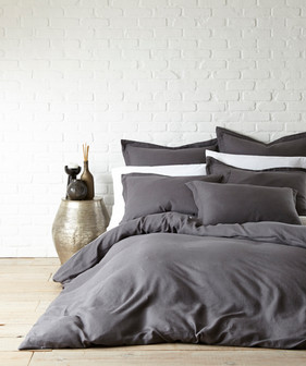Bedding Photography: Foot view of gray duvet on bed with pillows photographed against white brick wall.