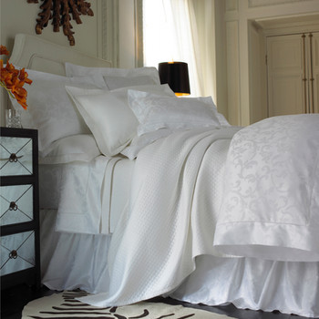 Bedding Photography: Low angle of white damask bedding for Neiman Marcus with matching white coverlet in white room.
