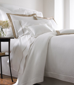 Bedding Photography: Low angle view of white coverlet bedding with brown striped pillow shams.