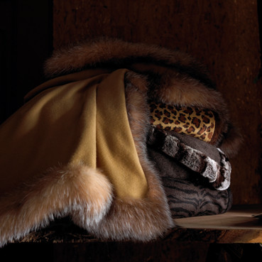 Bedding Photography: Softly draped fur throws shown in a stack in a dark environment.