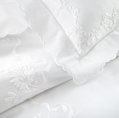 Bedding Photography: Close-up view of corner of scallopped white embroidered pillowcase and sheets for Loro Lino Linens.