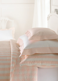 Bedding Photography: Three pink and white pillows with ping and white striped quilt on bed in white room.