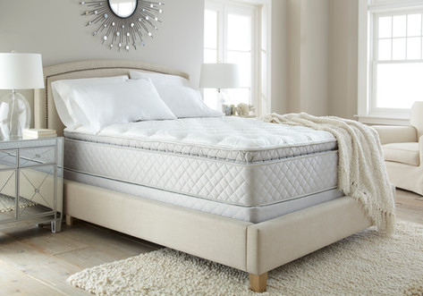 Bedding Photography: Dramatic view of quilted mattress in room scene on beige bed with rails and footboard.