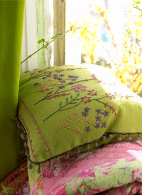 Bedding Photography: Cover photo of green embroidered pillow on pink and green duvet. Pillow is in window with sun hitting it from behind.