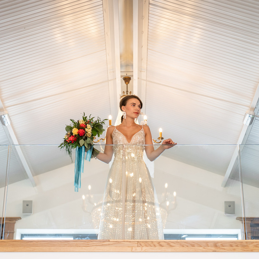 Bride with Wedding flowers and chandelier reflection
