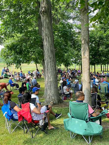 People sitting in lawn chairs distanced by household for an outdoor church service under the shade of trees.