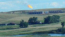 Bakken Fracking flares seen near a farm and pond - Photo via Emily Arasim/WECAN International