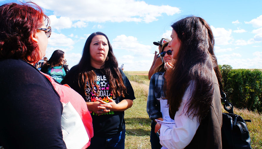 Osprey Orielle Lake (WECAN International) and Shannon Biggs (Movement Rights) speak with Kandi Mossett (Indigenous Environmental Network) while visiting a massive frack water spill site during the toxic tour