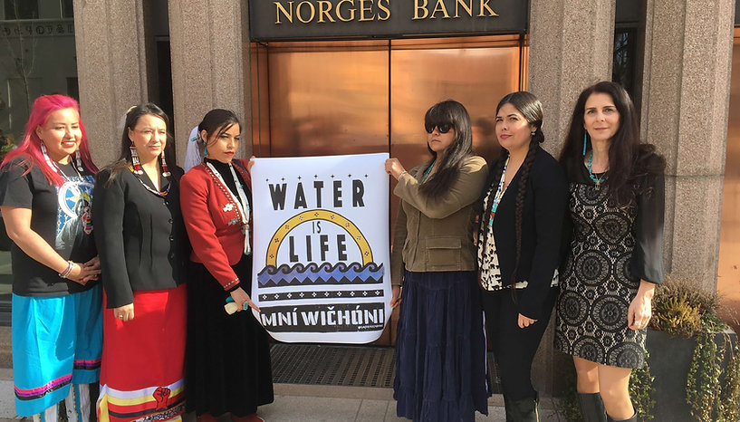 Indigenous Women's Divestment Delegation to Norway and Switzerland outside of Norges Bank before meeting with Norway's Government Pension Fund Global, Spring 2017.,(Left to right) Wasté Win Young, Dr.Sarah Jumping Eagle, Michelle Cook, Autumn Chacon, Tara Houska, with Delegate organizer, Osprey Orielle Lake