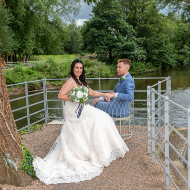 Seated wedding couple by the Derwent at West Mill, Darlay Abbey