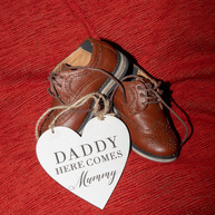 Cute page boy shoes and sign 'daddy here comes mummy'