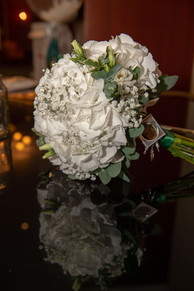 Bride's bouquet reflected on a shiny grand piano top