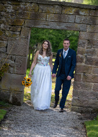 Bride and Groom walking through arch