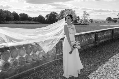 Beautiful black and white wedding photo of bride with her veil blowing in the breeze