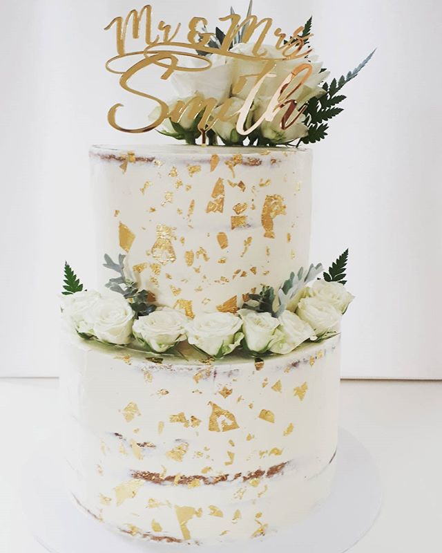 Classic semi naked wedding cake. Loving the fresh white florals with a touch of greenery and gold le