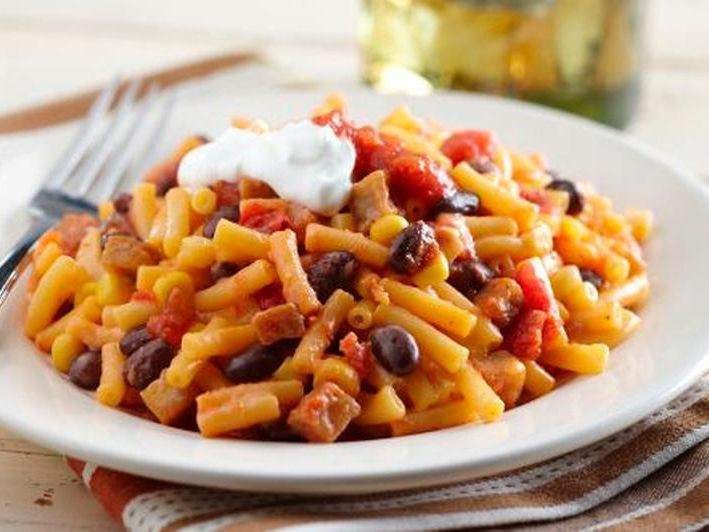 Macaroni and beans is a food with cheese and tomatoes and pasta made for boiling and cooking.