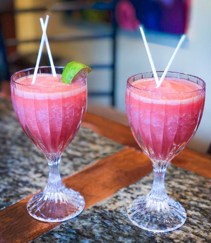 Two spicy watermelon cocktails with straws and lemon wedge