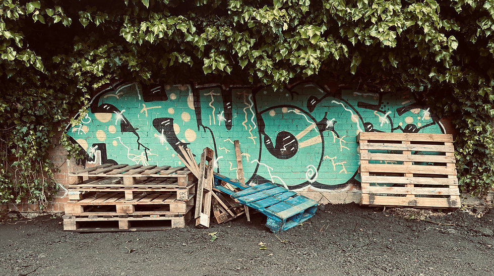 Pallets in front on blue graffiti
