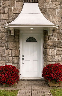 A white door with two red flower pots.jp