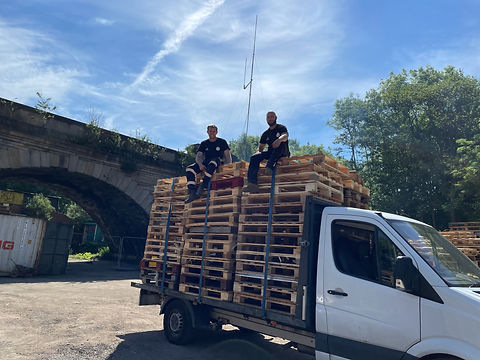 Two men sat on top of a van with pallets