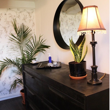 A black dresser with oils, plants, and a warm lamp resting on top.