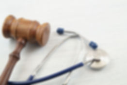 Judge's gavel and stethoscope on white w