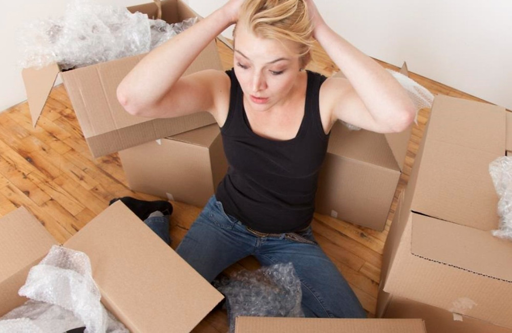 A frustrated blonde sitting on the floor with boxes all around her assuming she haven't finished packing her stuff yet.