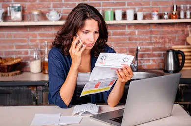 A woman frustrated with her bills sitting on the kitchen counter while holding a phone with her right hand and holding a bill on the other hand. She also seems to be talking to the phone on her hand.