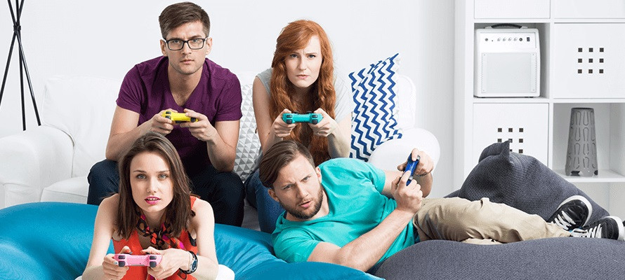 4 people what seems to be roommates are playing with their ps4 sitting together on a couch