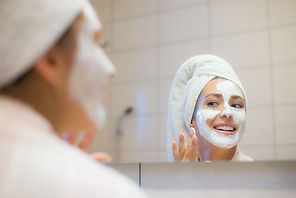 woman-putting-facial-mask-on-her-face-royalty-free-image-1623814377.jpeg