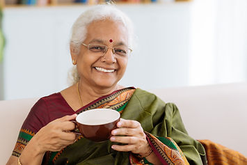 Cheerful Indian lady holding a big cup a