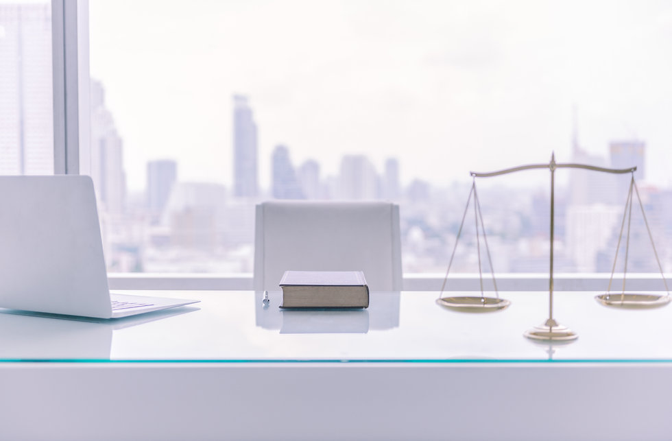 law books,computer and scales of justice on desk in lawyer office and city view..jpg