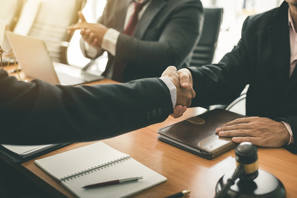 Businessman shaking hands to seal a deal with his partner lawyers or attorneys discussing