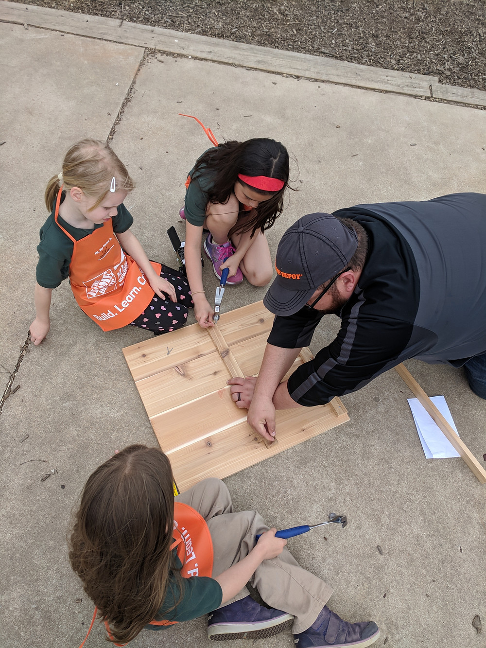 Students construct side of a garden box.