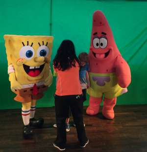 A kids club counselor getting the boys ready for a photo with Sponge Bob & Patrick.
