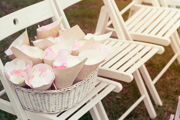 Basket with rose petals on the white cha