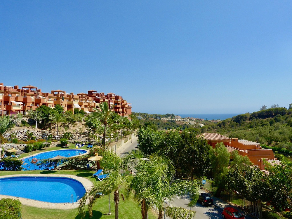 Views over swimming pools and a green valley towards the Mediterranean Sea