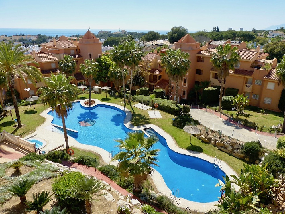 View over swimming pool and across residential properties towards the sea and Gibraltar