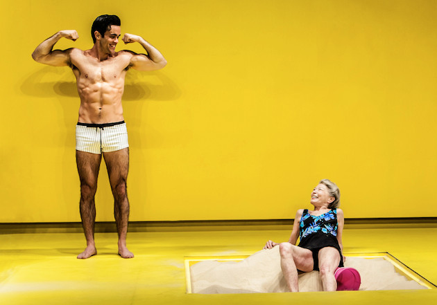 Against a yellow background, a half naked man is showing his muscle to an old lady in swimming suit lying in a sandbox