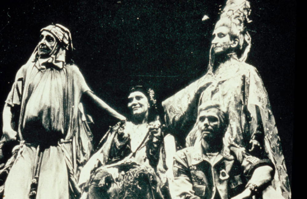 Four people, two standing with painted faces in loose robes, and two sitting on the stage.