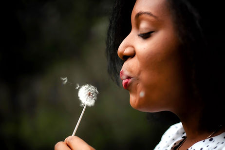 Happy woman blowing a dandelion
