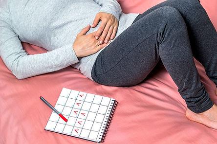 womanwith menstrual pain, calendar, pms, pink sheet, woman in grey long sleeve shirt, dark rey sweat pants