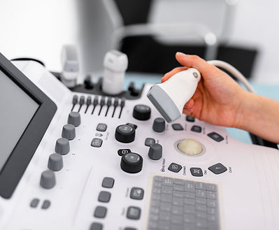white and grey ultrasound machine, hand holding part of the ultrasound
