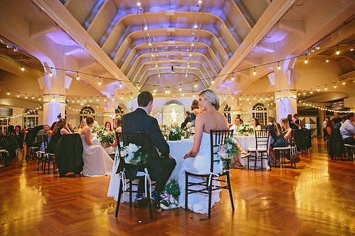 Henry ford museum wedding reception withe bride and groom facing their guests and purple uplighting.