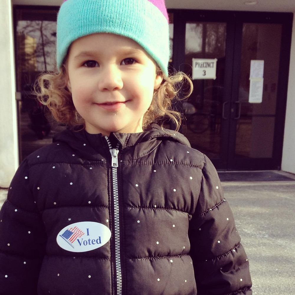 A child wears an I voted sticker in front of a voting precinct.