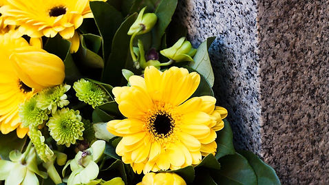 close up flowers with granite monument
