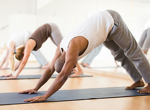 Portrait of focused man making yoga exercises with friends at fitness center.jpg