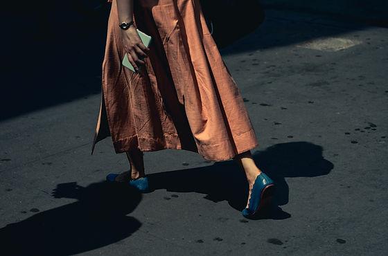 Mulher andando com sapatos azuis