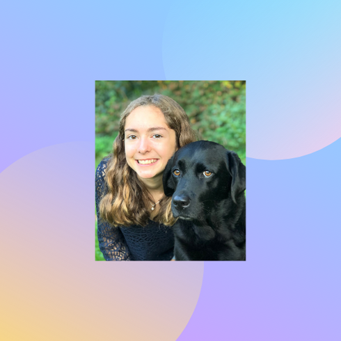 A portrait of Libby, a white woman, with her black labrador dog.