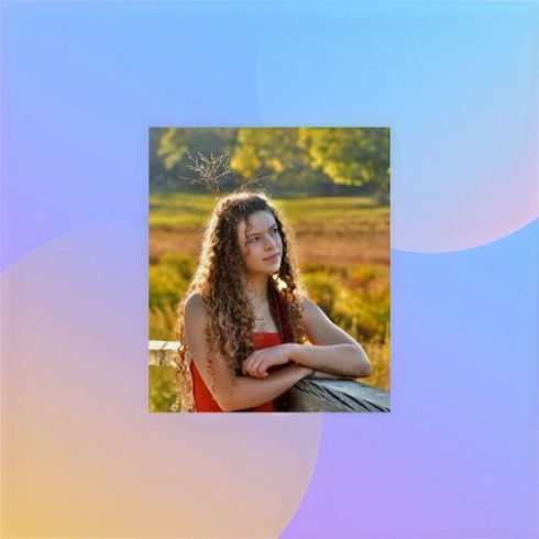 Willa is an 18 year old girl with long curly brown hair, a burgandy scarf and a red sleeveless top. She is leaning against a wooden railing and there is a blurred field in her background. She is smiling and looking into the distance slightly. There is a sprig of grass stuck in her hair.